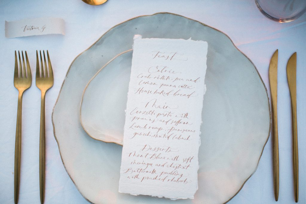 Dinner menu and scroll-style place card on elegant table setting