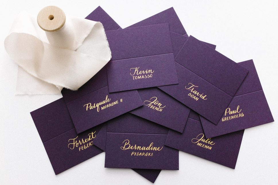 Purple place cards with gold ink calligraphy